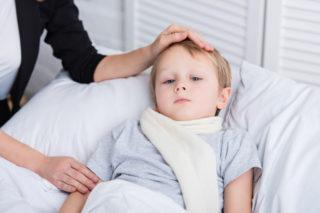 Matka pečuje o nemocného chlapce, který leží v posteli.