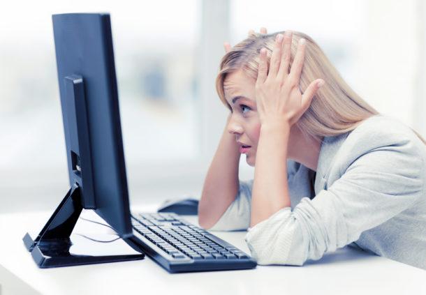 Zoufalá mladá žena s blond vlasy hledí na monitor počítače.